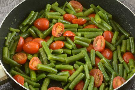 Grüne Bohnen und Traubentomaten mit Olivenöl in einer Pfanne sautiert Standard-Bild