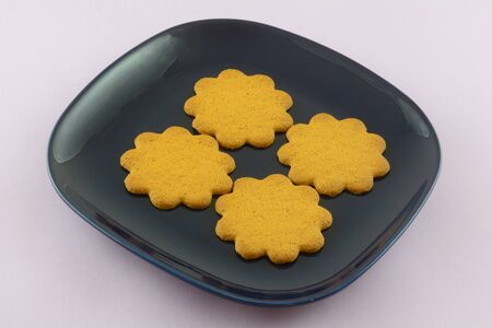 Swedish thin ginger cookies on blue plate on lavender background Archivio Fotografico