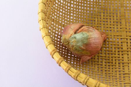 Rotting moldy shallot onion in woven basket on lavender background Archivio Fotografico
