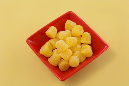 Yellow spice gum drops in red snack bowl on yellow background