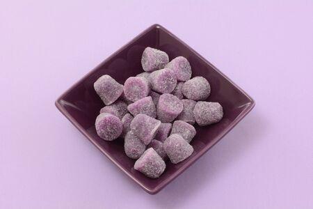 Purple gum spice drops in purple dessert bowl on lavender background