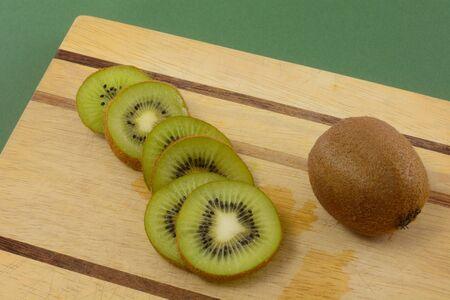 Kiwi slices and whole kiwi fruit on wooden cutting board on green background
