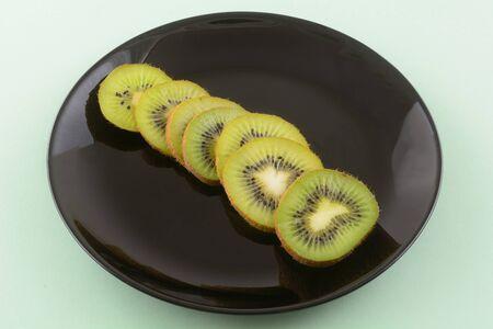 Raw fresh kiwi fruit slices on black plate on light green background
