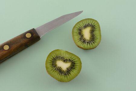 Kiwi fruit halves and kitchen knife on light green background