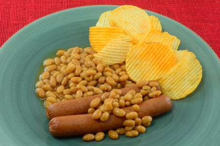 Meal of hot dogs and baked beans with flavored potato chips on blue plate Archivio Fotografico