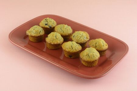 Mini blueberry muffins on red brunch plate on pink background