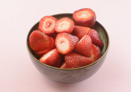 Ceramic bowl of freshly cut raw strawberries on pink background