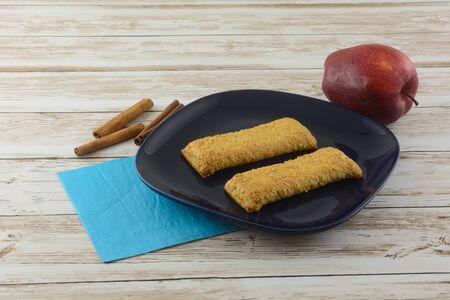 Two apple cinnamon breakfast bars on blue plate with apple cinnamon sticks and napkin Archivio Fotografico