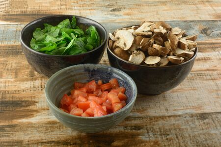 Ingredients of chopped spinach, mushrooms and tomatoes in ceramic bowls prepared for cooking Archivio Fotografico
