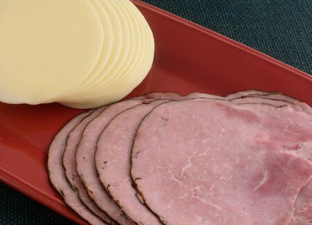 Stacks of black forest ham and provolone cheese scold cut slices on red platter Archivio Fotografico