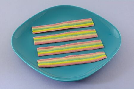 Chewy rainbow candy strips on blue dessert plate on lavender background