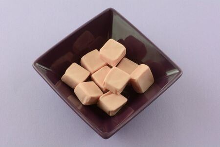 Strawberry toffee candy squares in purple candy bowl on lavender background
