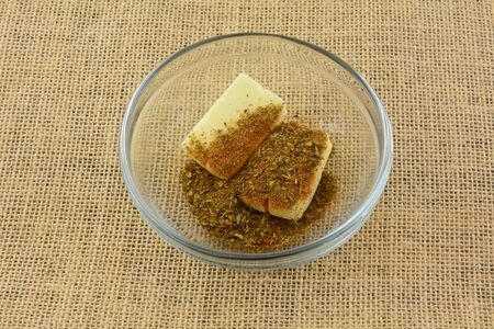 Two butter pats covered with dry chimichurri spice in glass mixing bowl Archivio Fotografico