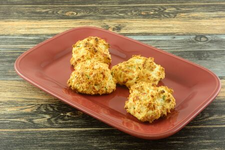 Homemade baked cheese and chive biscuits on red serving plate on table