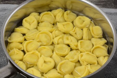 Close up of boiled cheese tortellini in stainless steel cooking pan Archivio Fotografico