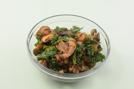 Sauteed mushrooms, kale and shallot filling or ingredient in glass bowl set aside for adding to dish Archivio Fotografico