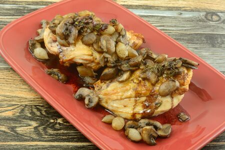 Baked chicken breasts in wine and vegetables of mushrooms and pearl onions in a red wine sauce