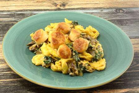 Scallops and cheese tortellini dinner on plate with shredded kale and sliced mushrooms on blue plate Archivio Fotografico