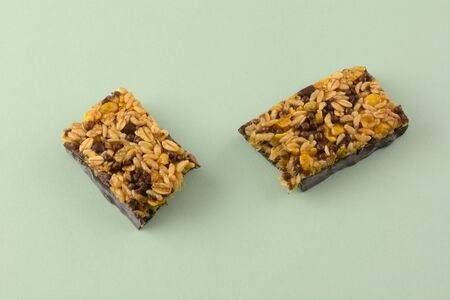Dark chocolate and rice candy bar snack halves on light green background