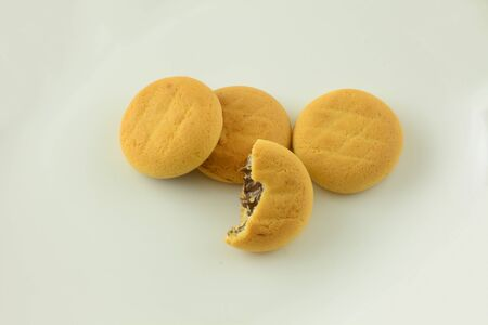 Soft baked cookies with chocolate filling and one with missing bite in white background