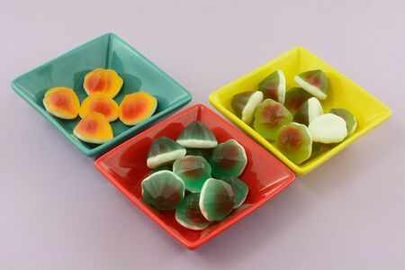 Sweet kiwi, lemon and blood orange gummy candies with sour apple filling in candy dishes on lavender background