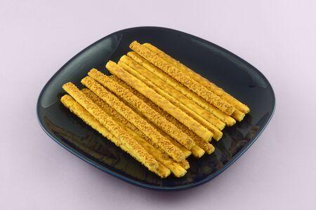 Pile of sesame bread sticks on blue snack plate on lavender background