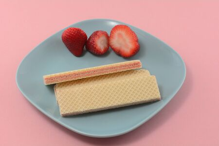 Strawberry sugar wafer cookies and fresh raw strawberries on blue snack plate on pink background
