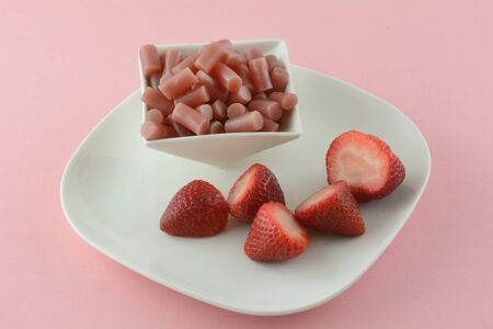 Fresh raw strawberries on white snack plate and strawberry licorice candy pieces in white candy dish on pink background