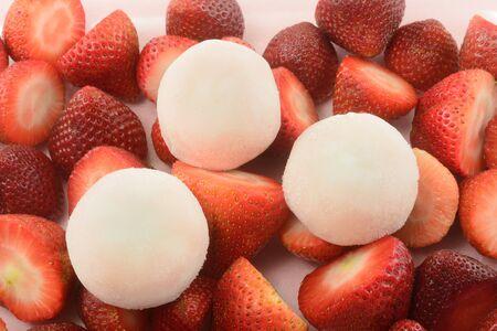 Strawberry ice cream mochi and fresh raw strawberries on pink background