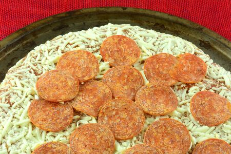 Closeup of frozen pepperoni and cheese pizza on weathered pizza pan