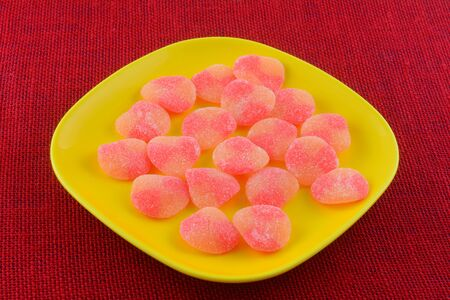 Closeup of sweet peach gummy candy pieces on yellow snack plate on red tablecloth