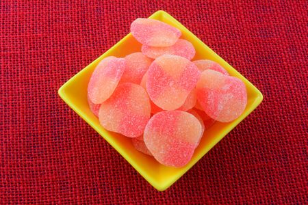 Closeup of sweet peach gummy candy pieces in yellow candy dish on red tablecloth Archivio Fotografico