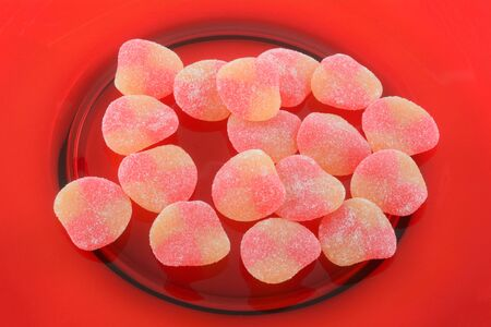 Closeup of sweet peach gummy candy pieces on red plate