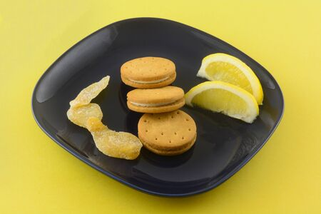 Cookies with lemon ginger cream filling  with lemon wedges and crystallized ginger on dark blue snack plate on yellow background