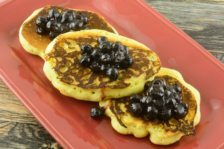 Cornmeal pancakes with jalapeno with blueberry sauce topping on red serving platter Archivio Fotografico