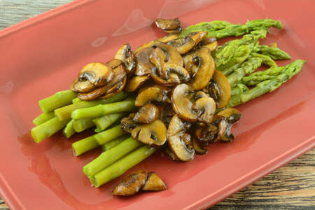 Cooked fresh asparagus with mushroom sauce on red serving plate