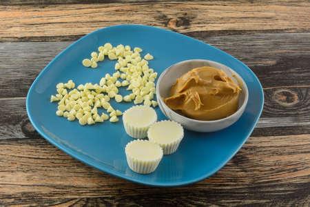 White chocolate peanut butter cups on blue plate with white chocolate chips and peanut butter in gray bowl Archivio Fotografico
