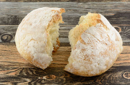 Broken round loaf of bread on table as symbol of consecrated bread for communion Stock Photo
