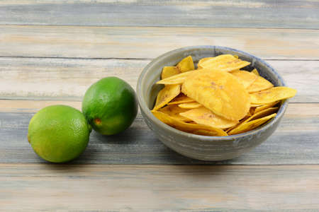 Lime flavored plantain chips in ceramic bowl and two fresh raw limes on table