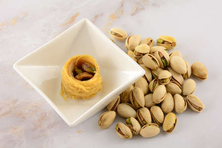 Piece of baklava bird's nest dessert with pistachio nuts inside placed in snack bowl with pistachio nuts