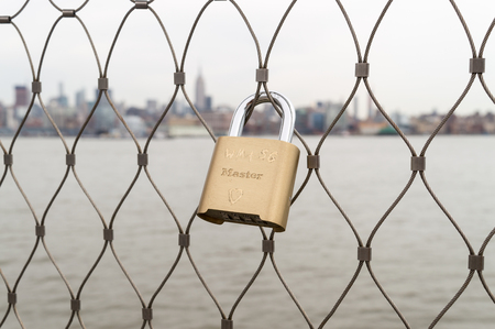 Lock engraved with heart and initials on the cell with Manhattan view on background.