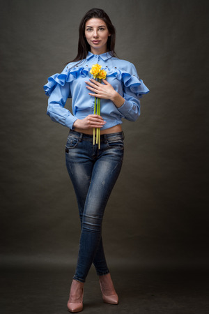 Portrait of a beautiful happy brunette woman in blue shirt holding yellow jonquils in her hands.
