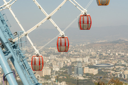 Ferris wheel part with red and yellow cabins against blue sky over the Tbilisi city.