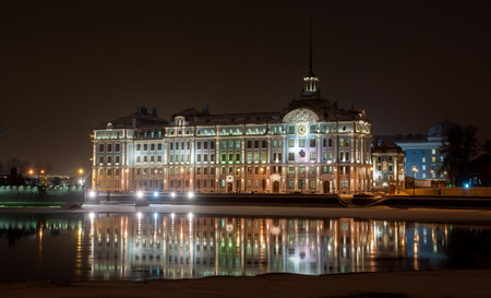 Nakhimov Naval School building with night illumination and its reflection in the winter river, St. Petersburg
