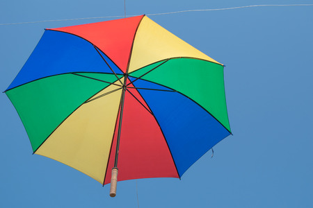 Colorful umbrella is hanging over head and blue sky background