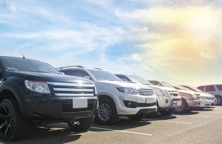 Car parked in large asphalt parking lot with white cloud and blue sky background. Outdoor parking lot with fresh ozone and green environment of travel transportation technology concept