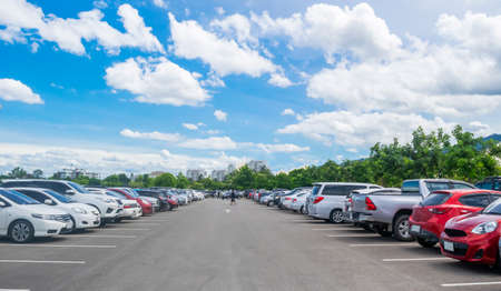 Car parking in large asphalt parking lot with trees, white cloud and blue sky background. Outdoor parking lot with fresh ozone and green environment of transportation and modern technology concept