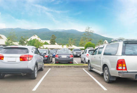 Car parked in asphalt parking lot and one empty space parking  in nature with trees, beautiful cloudy sky and mountain background .Outdoor parking lot with fresh ozone and green environment concept