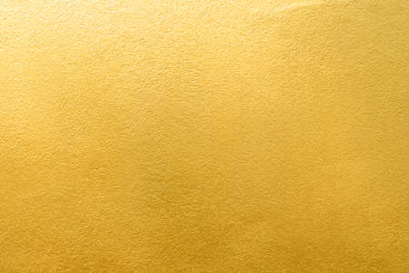 Gold wall texture background. Yellow shiny gold foil paint on wall surface with light reflection, vibrant golden luxury wallpaper Foto de archivo