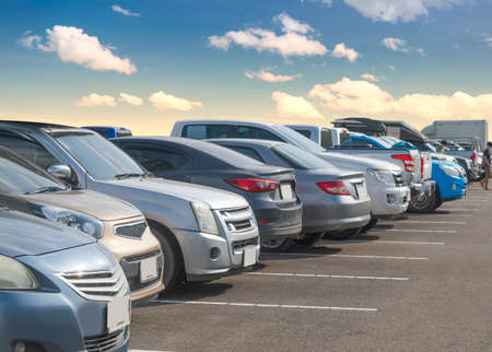 Car parking in large asphalt parking lot with white cloud and blue sky background. Outdoor parking lot with fresh ozone and green environment of transportation and modern technology concept